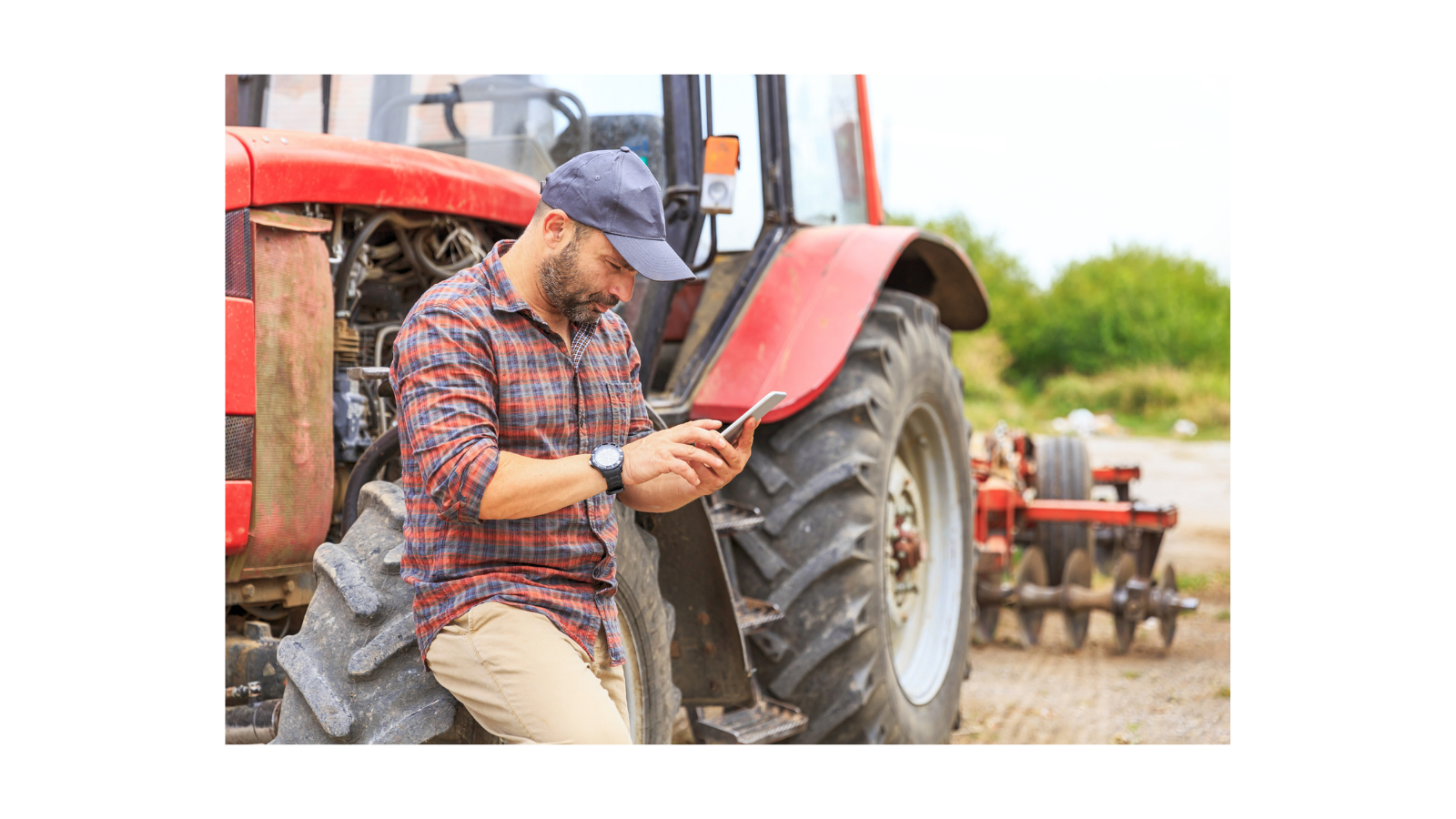 Farmer standing in front of a tractor with a phone in his hand