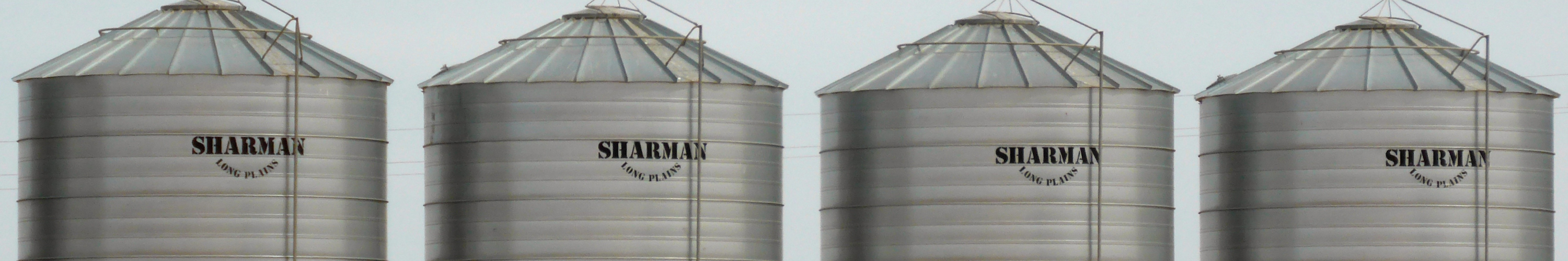 Four grain bins with blue skys in background.